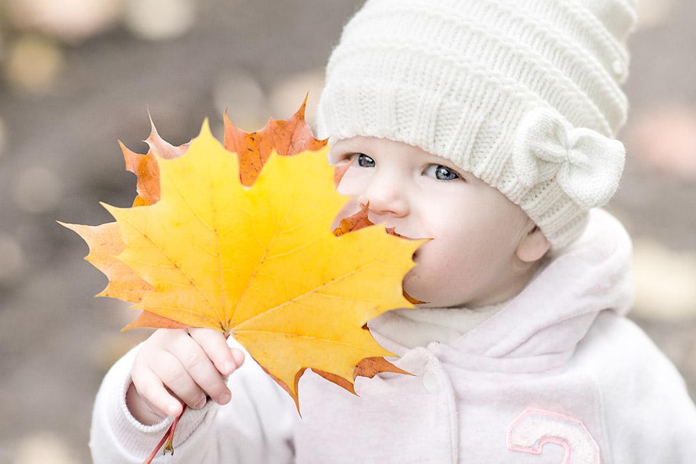 Kind mit Herbstlaub