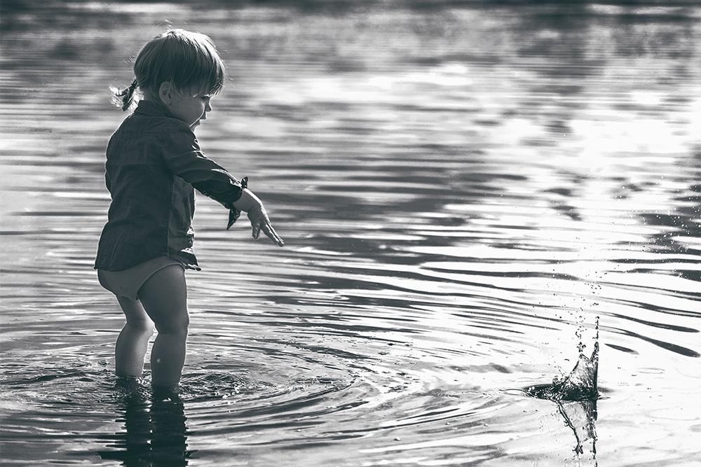 Kind, Steine ins Wasser werfen